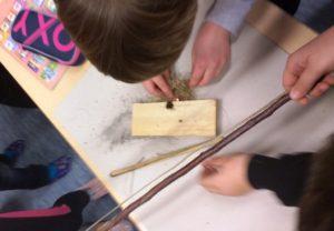 žáci rozdělávají oheň třením dřívek pomocí luku jako v pravěku
